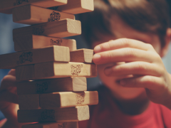 Boy playing with Jenga with curiosity. Photo credit: Michal Parzuchowski