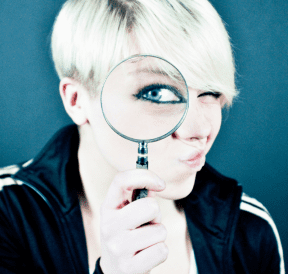 Do team-building programs work, woman looking through magnifying glass. Credit Emiliano Vittoriosi