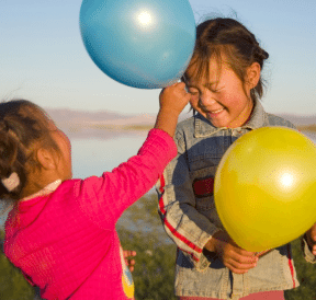 More play with two girls playing with balloons