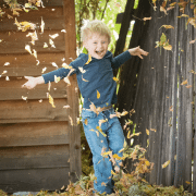 Boy playing with autumn leaves because play is making a comeback. Photo credit: Justin Young