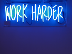 Work hard neon sign reflecting all work and no play motto. Photo credit: Jordan Whitfield