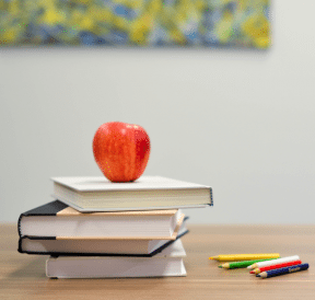 School books with apple to indicate back-to-school program time. Photo credit: Element5