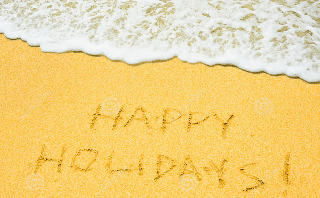 Happy holidays etched into sand at beach