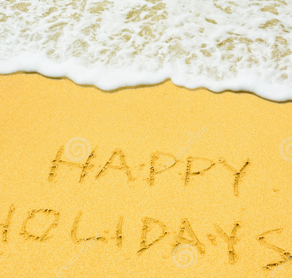 Happy holidays etched into sand at beach to wish everyone Merry Xmas