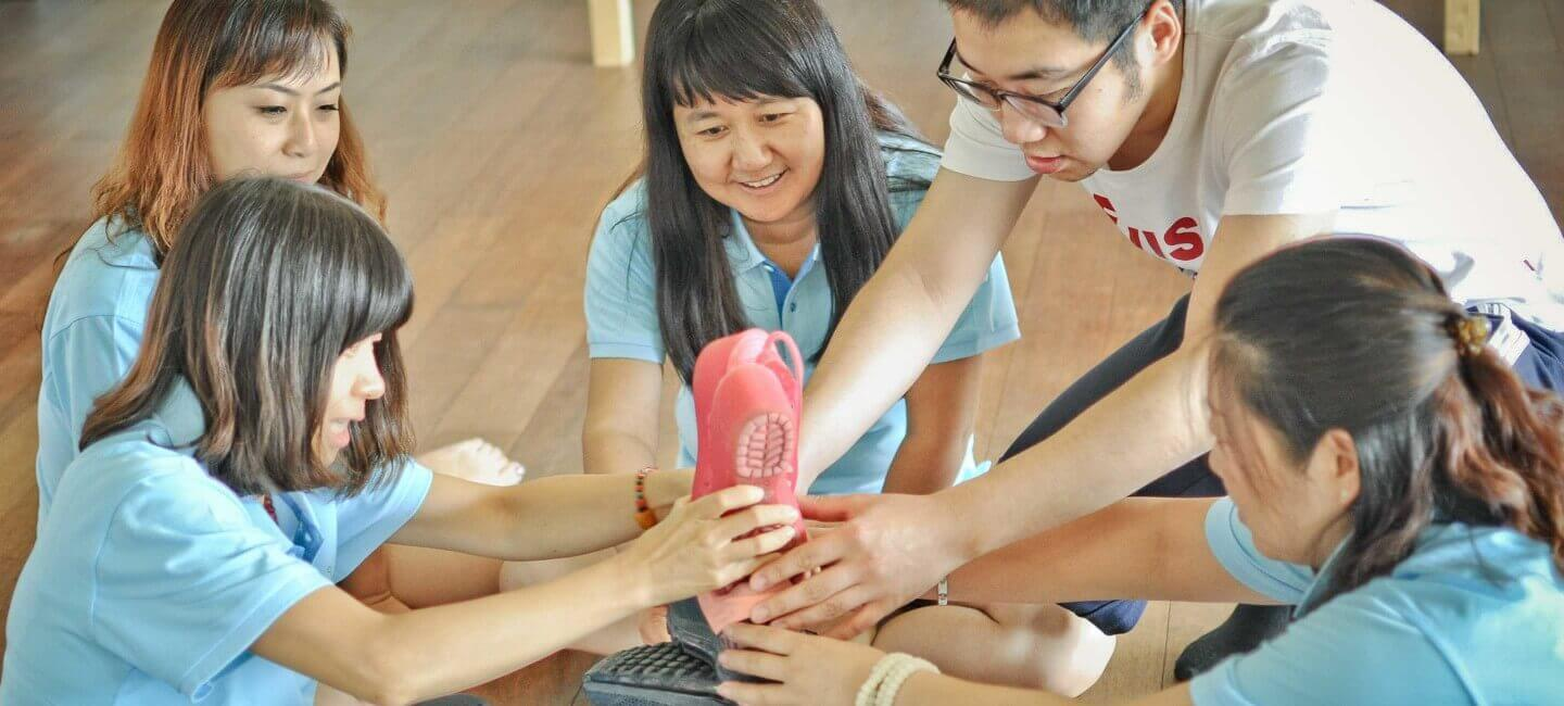 Team of Chinese teachers working together to build tall shoe tower