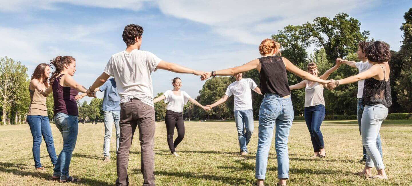 Group of young adults holding hands in a circle outside playing field