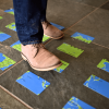 Man's foot about to step onto We! Discover Cards laying on floor