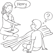Two people sitting either side of a dropped blanket facing one another, playing fun ice-breaker called Peek A Who