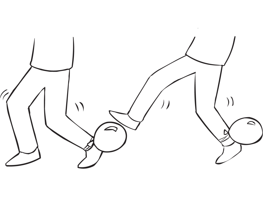 Person attempting to stand on the balloon tied to partner's ankle, in fun energiser called Balloon Tag