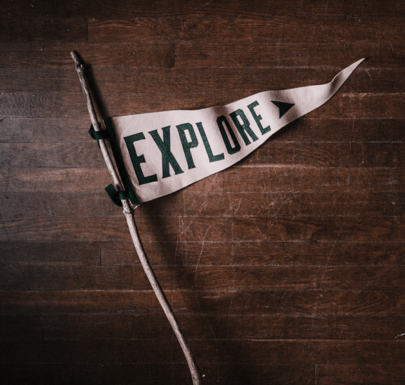 Old style flag which reads Explore. Photo credit: Andrew Neel