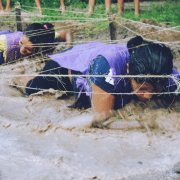 Honouring Challenge by Choice - two women completing a mud crawl