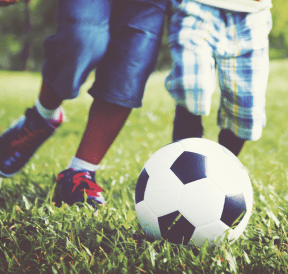 Two boys playing soccer portraying six simple principles of play