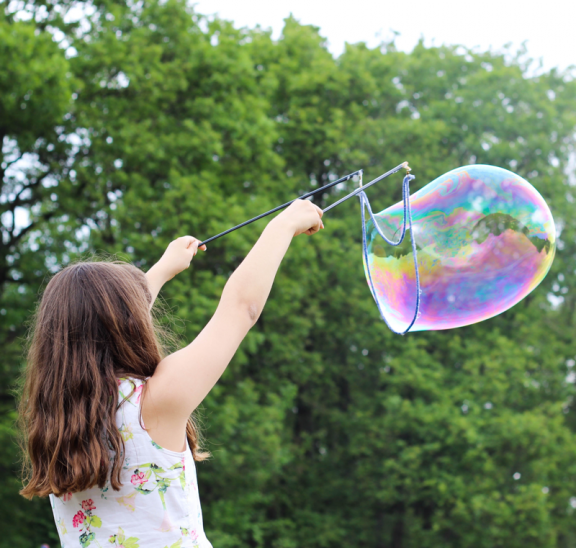 Girl blowing bubbles is playful state of mind. Photo credit Maxime Bhm