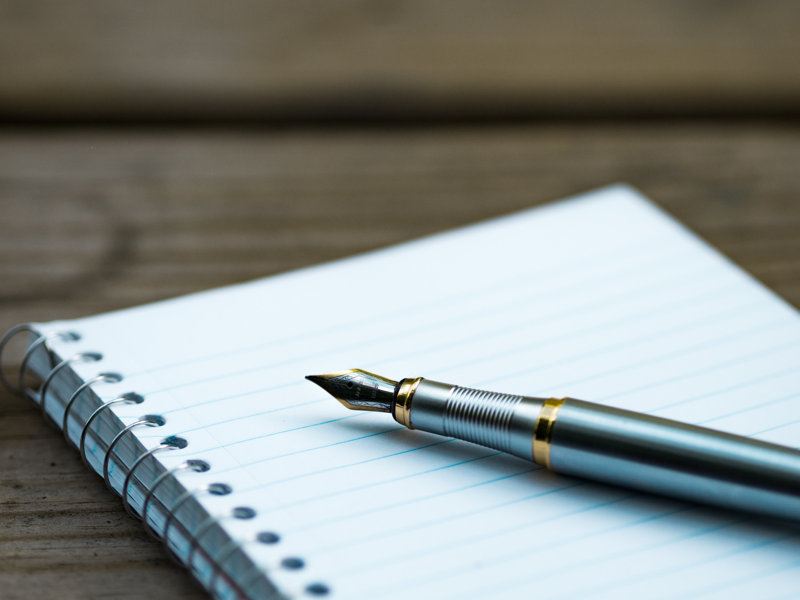 Pen writing four powerful questions on notepad. Credit Aaron Burden
