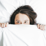 Manage your nerves better, woman hiding under bed sheets. Credit Alexandra Gorn
