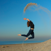 Woman jumping on beach showing ways to boost your energy