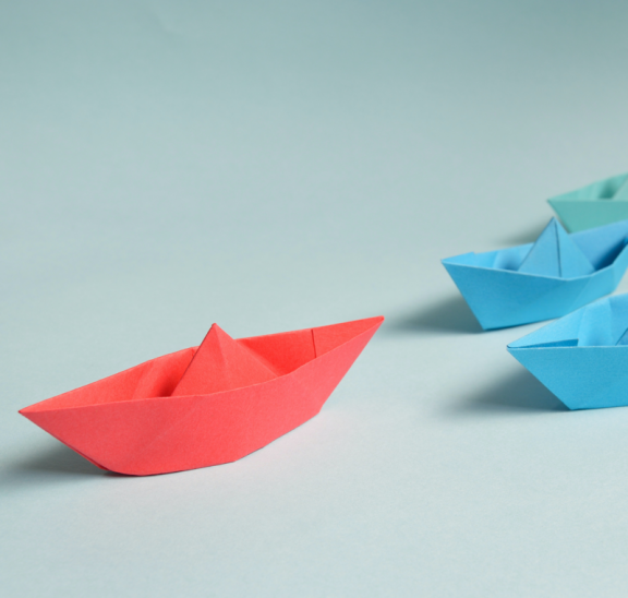 paper boats following a red lead paper boat team building activity