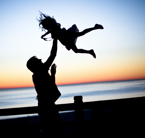 Man throwing child in air as part of team building trust activities they do together
