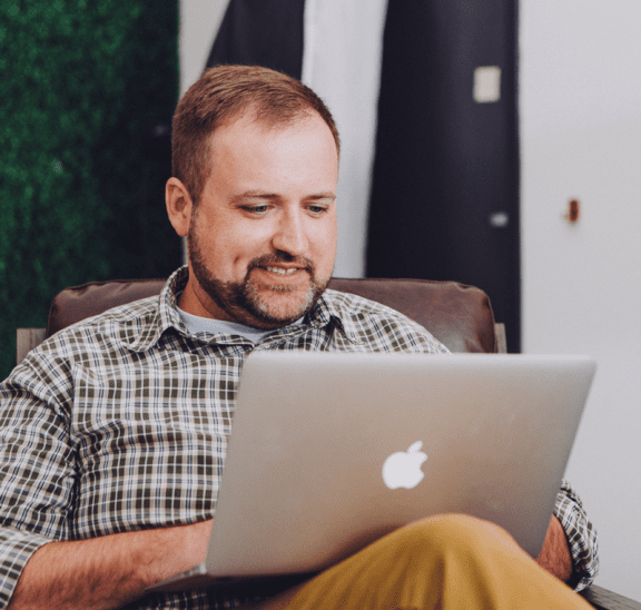 Man using laptop at home playing virtual trust building activities