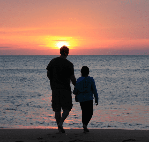 Father & child programs on the beach at sunset. Credit Emotionary App