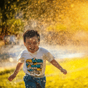 Boy running through sprinkler water game