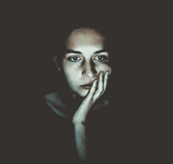 Woman sitting in dark with zoom fatigue. Credit Niklas Hamann