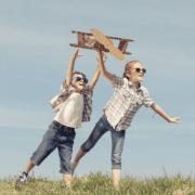 Power of fun with kids flying cardboard aeroplane
